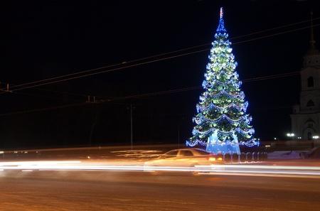 traffic on night road against  illuminated  Christmas tree at night city photo