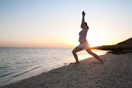 Beautiful young girl practicing yoga  against sunrise photo