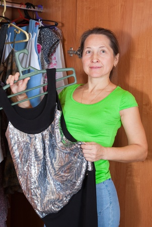 Mature woman chooses dress in wardrobe at her home Stock Photo - 8334022