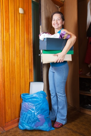 Mature woman taking away the garbage at home photo