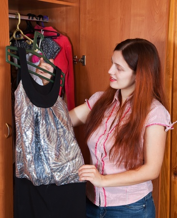 Girl looking at clothes in a closet photo