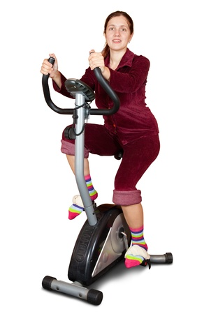 Young woman working out on exercycle. Isolated over white background photo