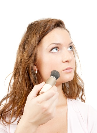 A young woman putting make up on her face with a brush, white background. photo