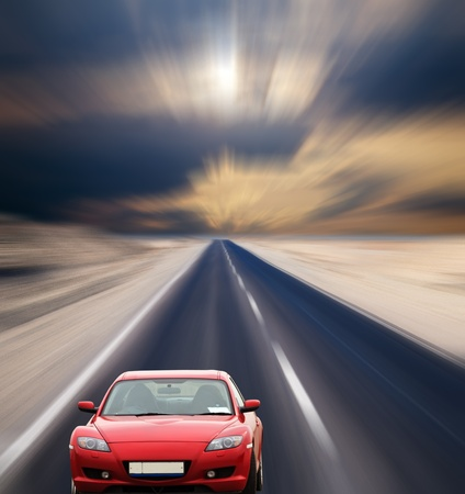 Red car on desert road under  cloudy sky