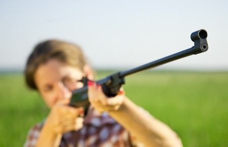 airgun: girl  aiming a pneumatic rifle against field. Focus on  barrel only