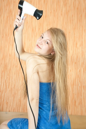 Girl dryes her long hair in home interior Stock Photo - 8382743