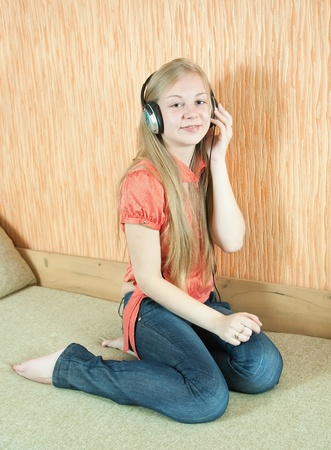 househould: Young beautiful happy girl listening music in headphones