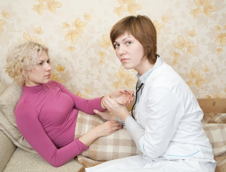 girl has her pulse taken by a caring female doctor on bed photo