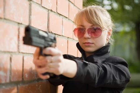 young woman aiming a black gun  near  the brick wall photo