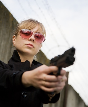 Female model performing glamour secret agent with gun Stock Photo - 8382535