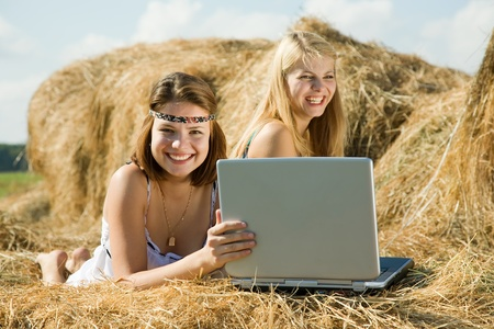 country girls with notebook laying on top of hay bail. Focus on brunette photo