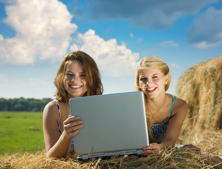 Young beautiful girls with   notebook  in farmland photo