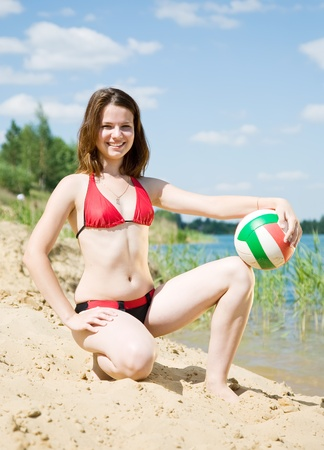 Portrait of sporty girl with volleyball in sand beach photo