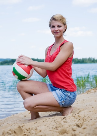 Beautiful beach volleyball female player with a ball photo