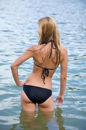 Rear view of girl in bikini standing in blue water photo