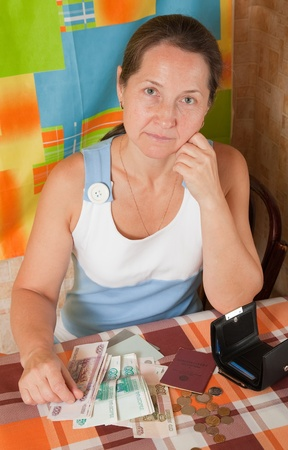 lamentable: Portrait of sad mature woman with money  at home