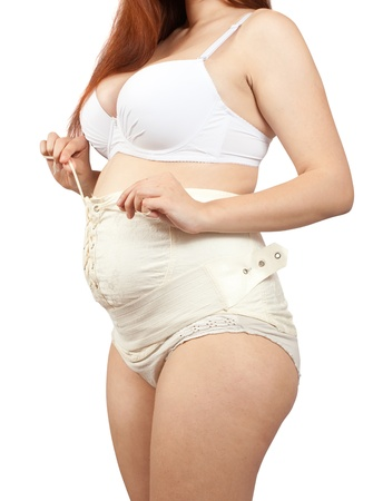 belly bandage:  Closeup of pregnant woman dressing obstetrical binder. Isolated over white