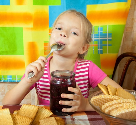 Little girl eating confiture from  glass jar at kitchen Stock Photo - 8520298