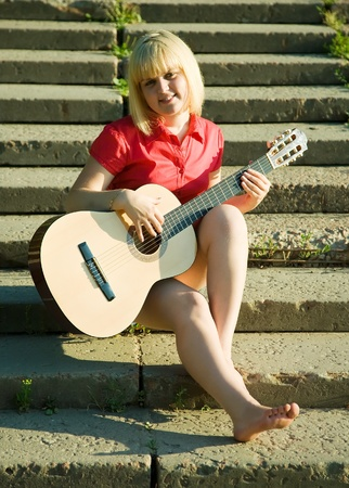 girl playing guitar: pretty girl playing guitar and relaxing  on steps of stair