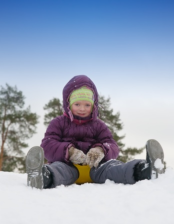Young girl riding in a park with a snow slide.  photo