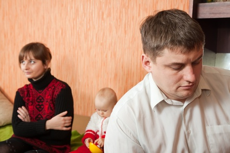 young marriage quarreling at home. Their baby sitting between them Stock Photo - 8524209