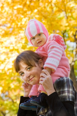 Happy mother with her baby against autumn nature photo