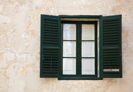 window with green shutters on old wall at mediterranean town photo