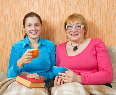 women and her adult daughter having tea  on sofa at home photo