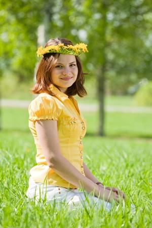 Brunette girl in  dandelion wreath at meadow Stockfoto
