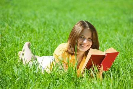 Relaxed girl lying on grass in meadow enjoying reading book photo