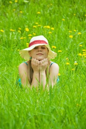 teener: Pretty smiling blonde girl relaxing in grass outdoor