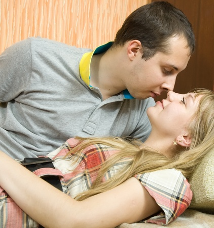 Young couple in love on sofa in  home interior photo