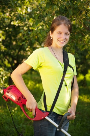 Girl works with hand grass-cutter in garden Stock Photo - 8591168