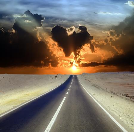 desert landscape: Road through desert landscape under cloudy sky