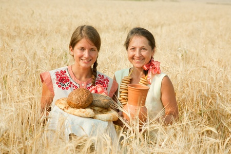 Women in traditional clothes with bread at rye field photo