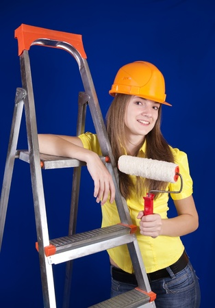 scaling ladder: Girl in hard hat with paint rollers near scaling-ladder