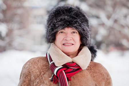 Outdoor winter portrait of mature woman in wintry clothes photo