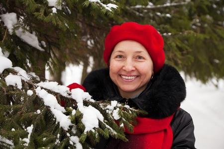 Outdoor winter portrait of mature woman near fir-tree Stock Photo - 8594216