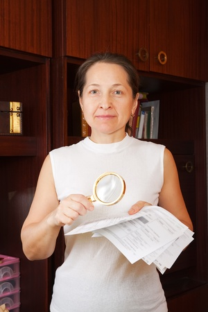 mature woman looking at utility bills through  magnifier  photo