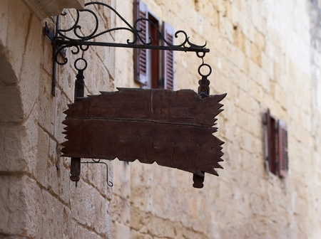 old wooden  plaque on wall old mediterranean street photo