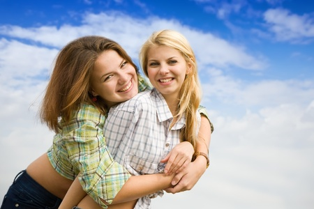 Two girls together against cloudy sky Stock Photo - 8594224