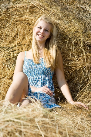 Portrait of country girl on hay in summer photo