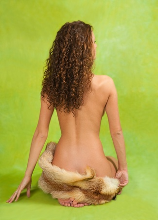 Rear view of a naked curly  girl  with fox fur over green Stock Photo