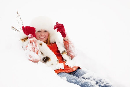Young woman lying on the  snow in winter photo