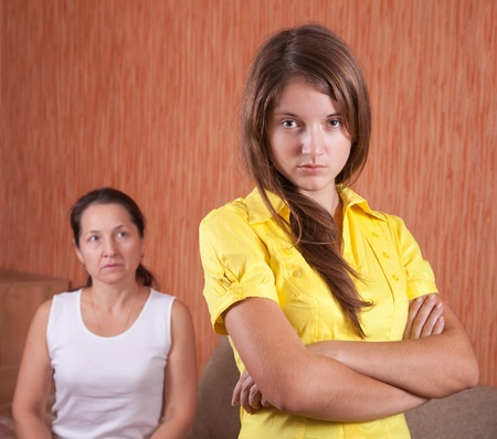 Mother and teen daughter having quarrel at home photo