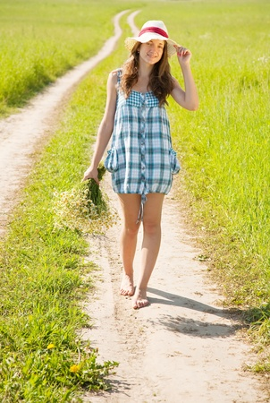 barefoot teens:  girl with bouquet of camomiles walking on country road