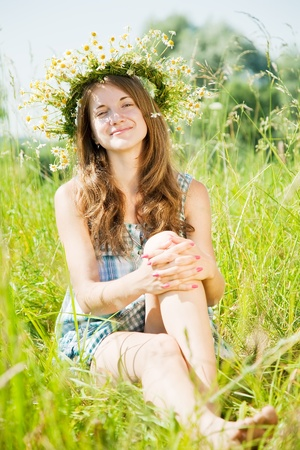 chaplet: long-haired   teen girl  in camomiles chaplet in grass Stock Photo