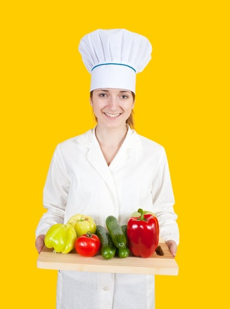 female cook with  vegetables on cutting board over yellow Stock Photo - 8692310