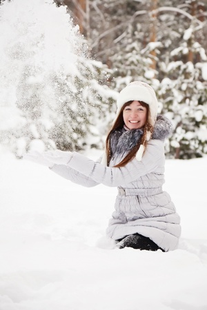 young woman throwing snow in the air  photo