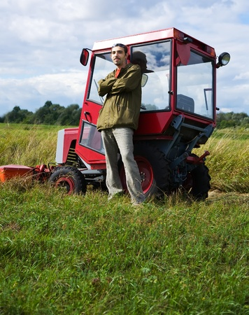 Farmer with tractor on meadow grass in summer day photo